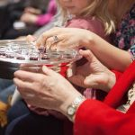 Photo of person passing communion tray.